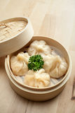 Chinese dumpling in a bamboo steamer box. On a wooden table Stock Image