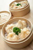 Chinese dumpling in a bamboo steamer box. On a wooden table Royalty Free Stock Photo