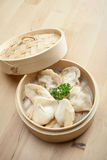 Chinese dumpling in a bamboo steamer box. On a wooden table Royalty Free Stock Photos