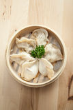 Chinese dumpling in a bamboo steamer box. On a wooden table Royalty Free Stock Images