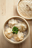 Chinese dumpling in a bamboo steamer box. On a wooden table Stock Photos