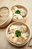 Chinese dumpling in a bamboo steamer box. On a wooden table Royalty Free Stock Image