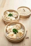 Chinese dumpling in a bamboo steamer box. On a wooden table Stock Images