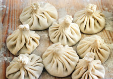 Chinese dumplings uncooked on wooden background. Street food booth selling Chinese specialty Steamed Dumplings. Royalty Free Stock Photo