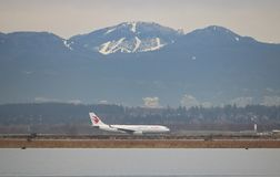Chinese Eastern Airlines in Vancouver Canada. A Chinese Eastern passenger jet passes ski hills in Vancouver, Canada as it takes off from Vancouver International stock photos