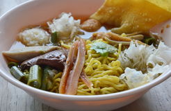 Chinese egg noodle with fish ball and crispy squid in soup Stock Photos