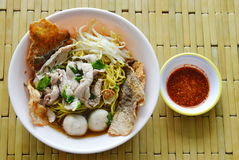Chinese egg noodle with pork ball topping crispy fish skin in soup and chili sauce Royalty Free Stock Photos