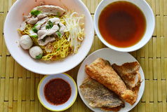 Chinese egg noodle topping pork ball and crispy fish skin with soup Royalty Free Stock Photo
