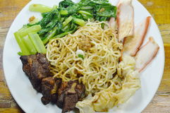Chinese egg noodles topping slice barbecue pork and stew rib with dumping dressing sweet black sauce on plate Stock Photo