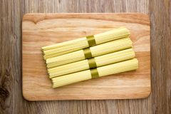 Dry egg noodles. Chinese egg noodles on a wooden board Stock Photos