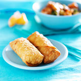 Chinese egg rolls on vibrant blue table setting Royalty Free Stock Photos