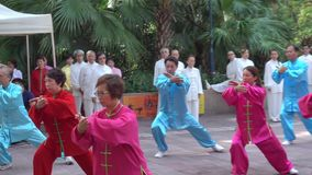 Chinese elders are performing Tai Chi in Kowloon Park.