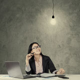 Chinese employee looking at bright lamp Stock Image