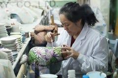 Chinese enamel handycraft  worker in factory Stock Image