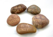Chinese and English Inspiration Stones. Inspirational words in a circular layout written in English and Chinese on pebbles stock image