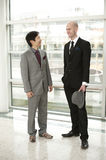 Chinese and European Business men conversing. A Chinese businessmen and European Businessmen conversing in a a relaxed menner. Business small talk Royalty Free Stock Images