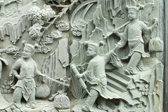 Chinese fable by stone carving. Chinese children play together by stone carving on temple wall royalty free stock photography