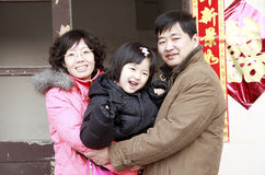 Chinese family. Young Chinese parents with their daughter in front of their home during new year. Chinese couplet on the wall means Double Happiness and a new stock image