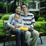 Chinese family. A chinese family photo, father,mother and baby are sitting on the bench Stock Photos