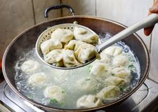 Chinese Family Cooking Boiled Dumplings in Wok Stock Photos