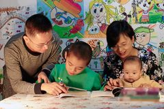 Chinese Family preschoolers education. Father teaching son and mother reading with baby girl, kids drawing in the background Stock Photo