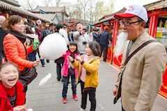 Chinese family has fun with cotton candy. Father with emperor beard made of cotton candy