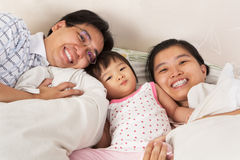Chinese family having fun on bed Stock Photos