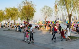 Chinese family holding a kite and kite stalls on yangtze riverside park in background Wuhan Hubei China royalty free stock photo