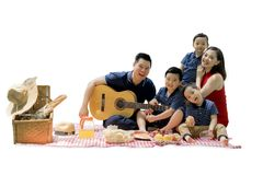 Chinese family picnicking with a guitar on studio. Picture of Chinese family enjoying holiday while picnicking and playing a guitar, isolated on white background royalty free stock image