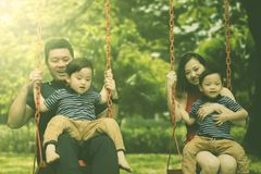 Chinese family playing swings in the playground. Picture of Chinese family looks happy while playing swings together in the playground Stock Photo