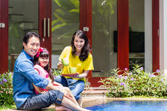 Chinese Family at pool in front of home. Or house drinking coffee Royalty Free Stock Photo