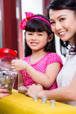 Chinese family saving money for college fund. Of child, putting coins in jar Royalty Free Stock Photos