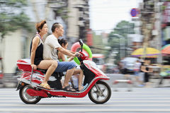 Chinese family on a scooter. XIANG YANG-CHINA-JULY 3, 2012. Couple with their child on a scooter on July 3, 2012 in Xiang Yang. China's family planning policy Stock Images