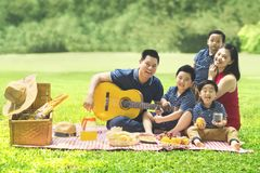 Chinese family singing together in the park. Chinese family smiling at the camera while playing a guitar and singing together in the park Royalty Free Stock Photos