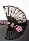 Chinese fan on black shiny surface Royalty Free Stock Photo