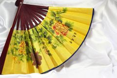 Chinese fan on a white silk background. Stock Photo