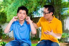 Chinese father gives his son some advice. Chinese Asian father talking to his son but he will not listening, holding his ears with his hands refusing the good Stock Image