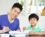 Chinese Father And Son Sitting At Home Eating. A Meal Royalty Free Stock Photos