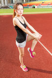 Chinese female athelete stretching legs on sports field, warming Stock Image