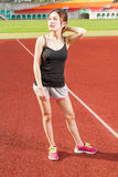 Chinese female athelete stretching on sports field royalty free stock photography