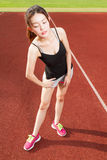 Chinese female athelete stretching on sports field Stock Photo
