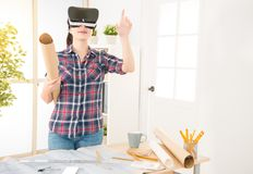 Chinese female designer watch 3D model by VR. Chinese Asian young female interior designer put on VR watching 3D model product while at the desk in creative Royalty Free Stock Photos