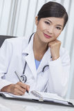 Chinese Female Woman Hospital Doctor Writing In Office. A Chinese Asian female medical doctor writing in a hospital office Royalty Free Stock Photography