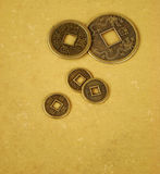 Chinese feng shui coins. For good fortune and success in old and worn textile background stock images