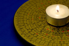 Chinese Feng Shui compass. With the candle isolated on blue stock photography