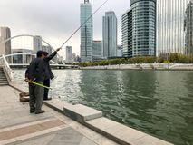 Fishermans on the embankment of the river Haihe in Tianjin downtown, China. stock photo