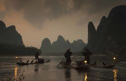 Chinese fishermen on the boat in mountains. Chinese fishermen on the boat in fog and rainy mountains Stock Image