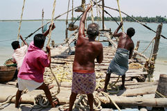 Chinese fishing nets, #3. Indians pulling the rope, arising the Chinese fishing nets, Fort Cochin, Kherala, India Royalty Free Stock Photos