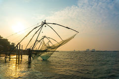 Chinese fishing nets on the shore of the Arabian Sea. Fort Cochin, Kerala, India. Historic Landmark. Warm evening. Scenic contours in the sunset twilight Stock Images