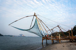 Chinese Fishing nets and small ship at dramatic sunset sky background Stock Images